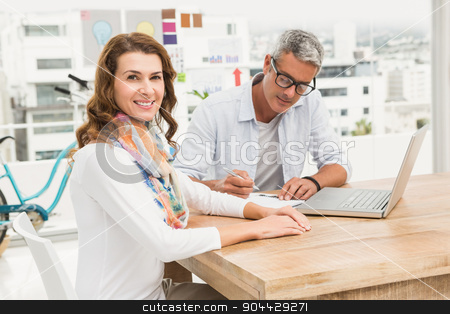 Smiling casual designer in front of her working colleague stock photo, Portrait of smiling casual designer in front of her working colleague in the office by Wavebreak Media