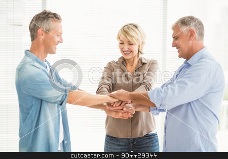 Smiling business colleagues stacking hands stock photo, Three smiling business colleagues stacking hands together at the office by Wavebreak Media
