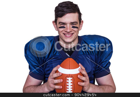 Smiling american football player holding a ball stock photo, Portrait of a smiling american football player on a white background by Wavebreak Media