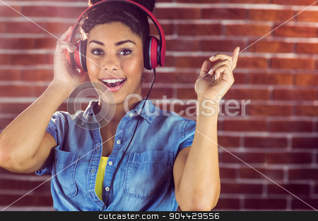 Portrait of young woman smiling at her song stock photo, Portrait of young woman smiling at her song on a red brick wall by Wavebreak Media