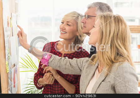 Smiling business team pointing a note on the wall stock photo, Smiling business team pointing a note on the wall at office by Wavebreak Media