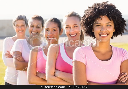 Smiling women wearing pink for breast cancer with arms crossed stock photo, Portrait of smiling women wearing pink for breast cancer with arms crossed in parkland by Wavebreak Media