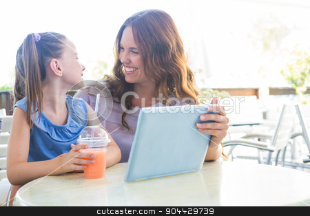 Mother and daughter using tablet at cafe terrace stock photo, Mother and daughter using tablet at cafe terrace on a sunny day by Wavebreak Media