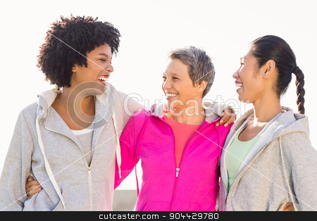 Laughing sporty women with arms around each other stock photo, Laughing sporty women with arms around each other in parkland by Wavebreak Media