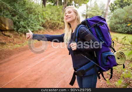 Pretty hitchhiker sticking thumb out stock photo, Pretty hitchhiker sticking thumb out on a crossing path by Wavebreak Media