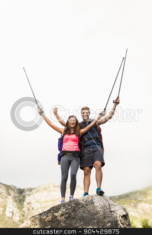Young happy joggers standing on rock cheering stock photo, Young happy joggers standing on rock cheering in the nature by Wavebreak Media