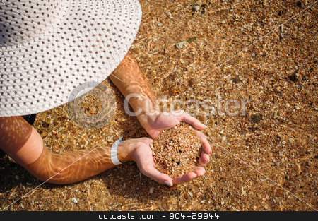 young woman in a big hat holding a sand stock photo, Elegant Beautiful Woman in straw hat on the Beach. Young woman in a big hat holding a sand by timonko