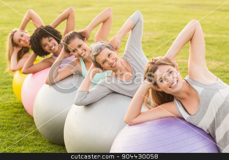 Smiling sporty women working out with exercise balls stock photo, Portrait of smiling sporty women working out with exercise balls in parkland by Wavebreak Media
