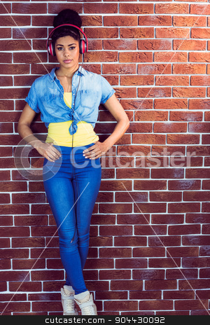 Portrait of a pretty young woman with headphones  stock photo, Portrait of a pretty young woman with headphones leaning against a red brick wall by Wavebreak Media