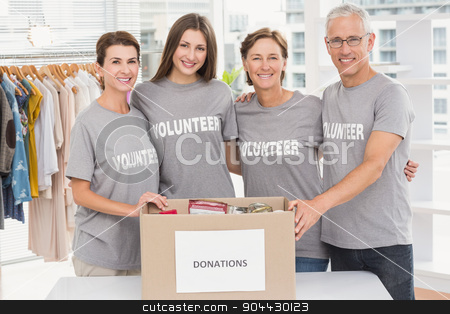 Smiling volunteers putting arms around each other stock photo, Portrait of smiling volunteers putting arms around each other in the office by Wavebreak Media