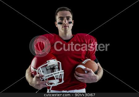American football player holding helmet stock photo, American football player holding helmet and american ball by Wavebreak Media