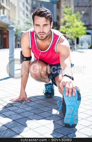 Handsome athlete doing a leg stretching stock photo, Handsome athlete doing a leg stretching on a sunny day by Wavebreak Media