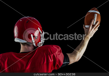 Rear view of american football player holding up football stock photo, Rear view of american football player holding up football against black background by Wavebreak Media