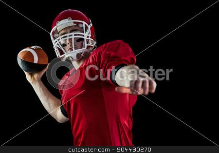 American football player throwing football stock photo, American football player throwing football against black background by Wavebreak Media