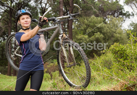 Athletic blonde carrying her mountain bike stock photo, Athletic blonde carrying her mountain bike in the nature by Wavebreak Media