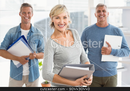 Smiling business colleagues holding workbooks stock photo, Portrait of smiling business colleagues holding workbooks at office by Wavebreak Media