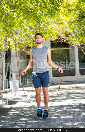 Handsome athlete doing jumping rope stock photo, Portrait of an handsome athlete doing jumping rope on a sunny day by Wavebreak Media