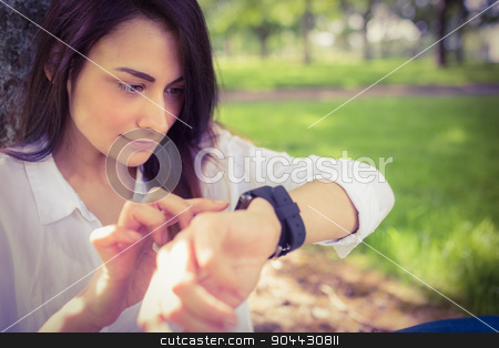 Beautiful brunette using smartwatch in the park stock photo, Beautiful brunette using smartwatch in the park on a sunny day by Wavebreak Media