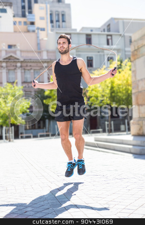 Handsome athlete doing jumping rope stock photo, Handsome athlete doing jumping rope on a sunny day by Wavebreak Media