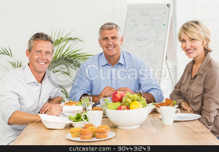 Smiling business colleagues having lunch together stock photo, Portrait of business colleagues having lunch together at office by Wavebreak Media