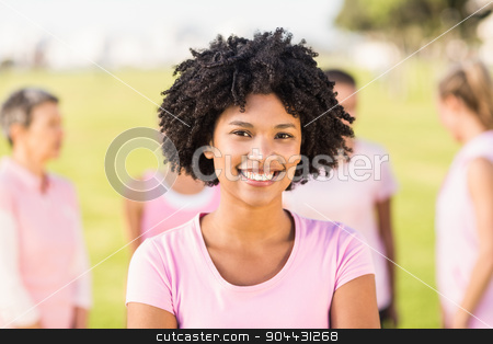 Smiling young woman wearing pink for breast cancer in front of f stock photo, Portrait of smiling young woman wearing pink for breast cancer in front of friends in parkland by Wavebreak Media