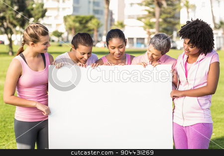 Women wearing pink for breast cancer and holding blank poster stock photo, Women wearing pink for breast cancer and holding blank poster in parkland by Wavebreak Media