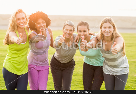 Smiling sporty women doing thumbs up stock photo, Portrait of smiling sporty women doing thumbs up in parkland by Wavebreak Media