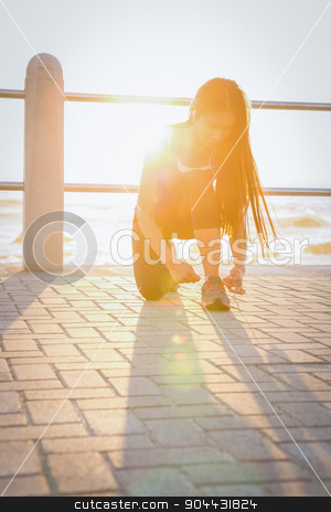 Fit woman tying her shoelace at promenade stock photo, Fit woman tying her shoelace at promenade on a sunny day by Wavebreak Media