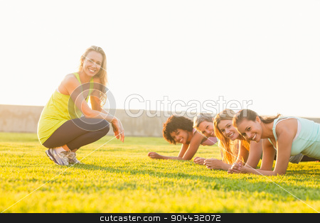 Smiling sporty women planking during fitness class stock photo, Portrait of smiling sporty women planking during fitness class in parkland by Wavebreak Media