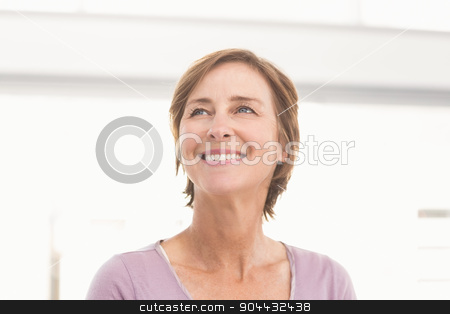 Smiling casual businesswoman looking away stock photo, Smiling casual businesswoman looking away in the office by Wavebreak Media