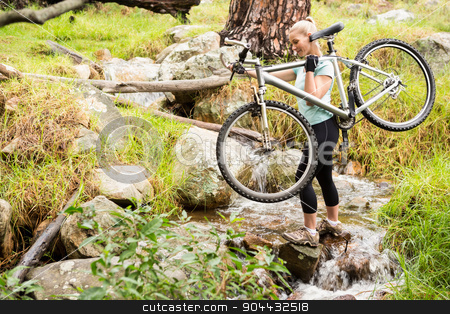 Serious fit woman lifting her bike stock photo, Serious fit woman lifting her bike while crossing a river by Wavebreak Media