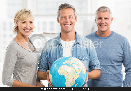 Smiling businessman holding terrestrial globe stock photo, Portrait of a smiling businessman holding terrestrial globe at office by Wavebreak Media