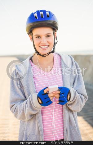 Smiling sporty blonde skater enjoying music stock photo, Portrait of smiling sporty blonde skater enjoying music at promenade  by Wavebreak Media