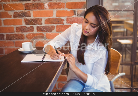 Smiling businesswoman having coffee and planning her week stock photo, Smiling businesswoman having coffee and planning her week in a cafe by Wavebreak Media