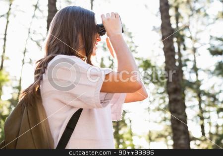 Smiling brunette hiker looking through binoculars stock photo, Smiling brunette hiker looking through binoculars in the nature by Wavebreak Media
