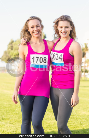 Two smiling blondes supporting breast cancer marathon stock photo, Portrait of two smiling blondes supporting breast cancer marathon in parkland by Wavebreak Media