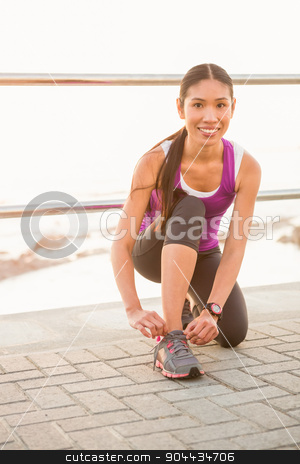 Smiling fit woman tying shoelace at promenade stock photo, Portrait of smiling fit woman tying shoelace at promenade on a sunny day by Wavebreak Media