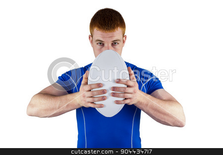 Rugby player holding rugby ball stock photo, Portrait of a rugby player holding rugby ball on a white background by Wavebreak Media