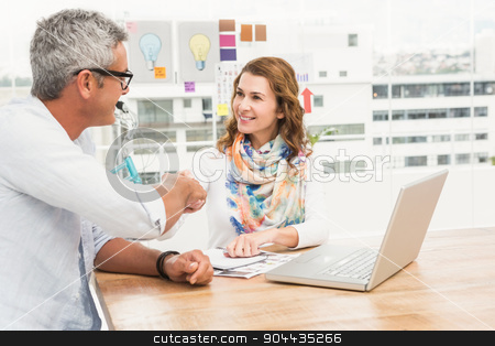 Smiling casual designers sitting and handshaking  stock photo, Smiling casual designers sitting and handshaking in the office by Wavebreak Media