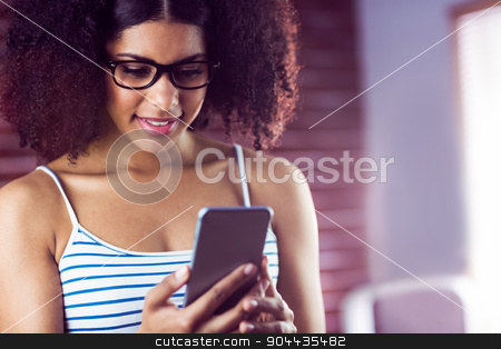 Happy hipster using her phone stock photo, Happy hipster using her phone in a studio  by Wavebreak Media