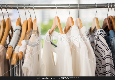 Clothes on clothes rail stock photo, Clothes on clothes rail in clothing store by Wavebreak Media