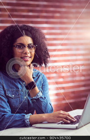 Casual businesswoman using laptop and smartwatch stock photo, Casual businesswoman using laptop and smartwatch in her office by Wavebreak Media