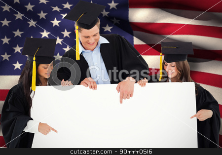 Composite image of three graduates pointing to the blank sign stock photo, Three graduates pointing to the blank sign against digitally generated american national flag by Wavebreak Media