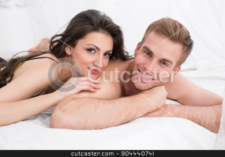Happy young couple lying in white bed stock photo, Happy young couple lying in white bed, looking at the camera. Girl hugging guy. Morning light. by bezikus