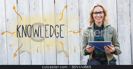 Knowledge against smiling blonde in glasses using tablet pc stock photo, The word knowledge against smiling blonde in glasses using tablet pc by Wavebreak Media