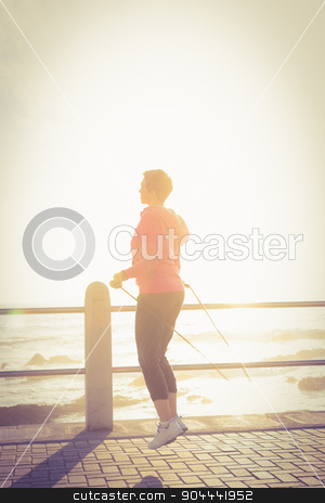 Sporty woman skipping at promenade stock photo, Sporty woman skipping at promenade on a sunny day by Wavebreak Media