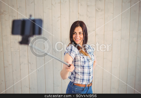 Pretty hipster taking a selfie with stick stock photo, Pretty hipster taking a selfie with stick on wooden planks background by Wavebreak Media