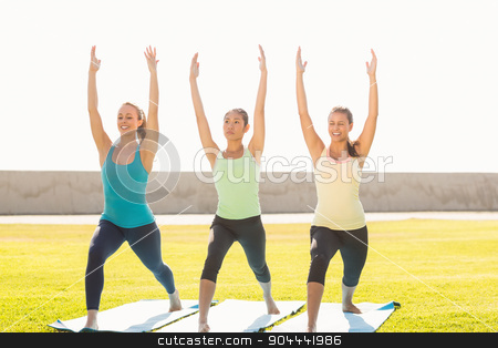 Smiling sporty women doing yoga together stock photo, Smiling sporty women doing yoga together in parkland by Wavebreak Media