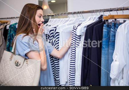 Brunette shocked by price of clothing stock photo, Brunette shocked by price of clothing in fashion boutique by Wavebreak Media