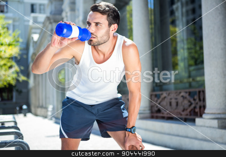 Tired handsome athletic drinking out of bottle stock photo, Tired handsome athletic drinking out of bottle in the city by Wavebreak Media